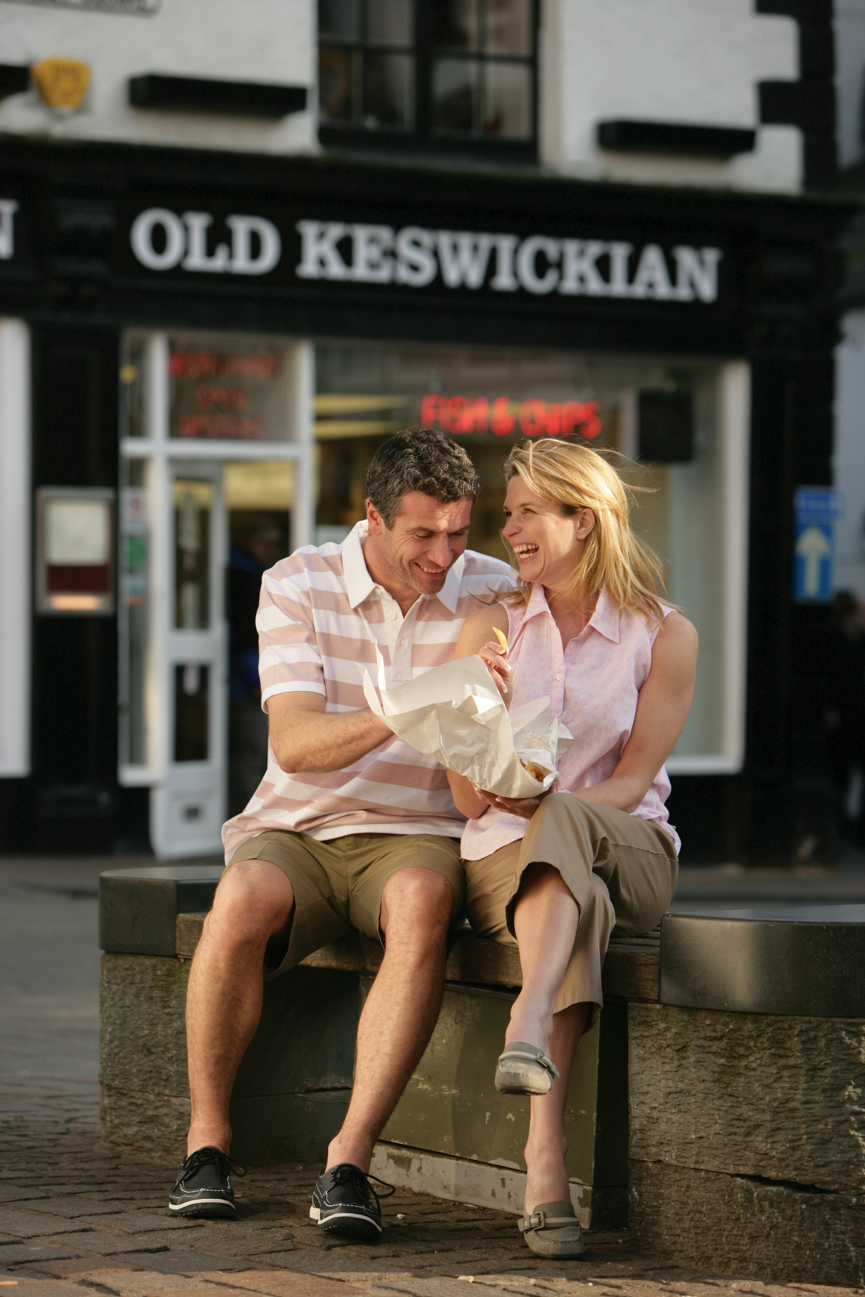 Couple eating fish and chips in Keswick Town Centre.