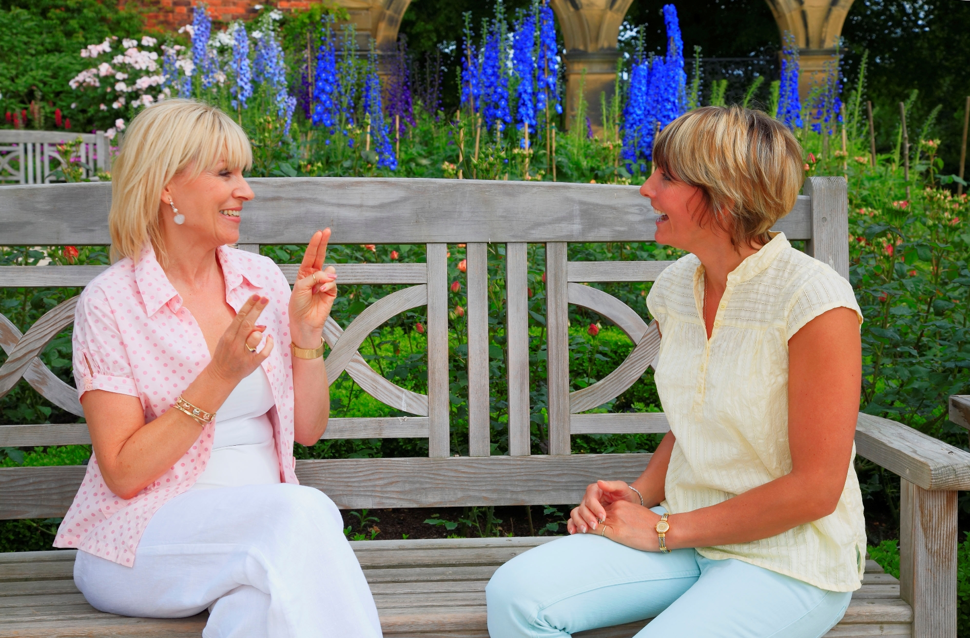 Two women, sat on a wooden bench, conversing in sign language within the formal floral surroundings of the Alnwick Garden. This developing garden is the inspiration of Jane, Duchess of Northumberland whose vision is to develop it into a contemporary garden that integrates water and light into a theatre of gardens.
