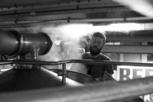 A man brewing beer in black and white